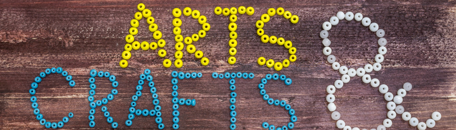 """""""Arts & Crafts"""" written in beads on a wooden background"""